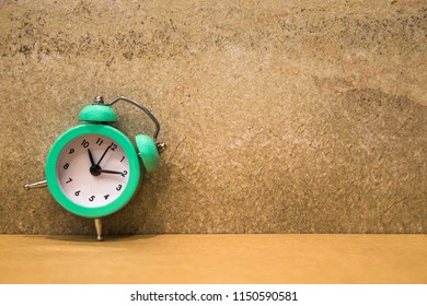 Green alarm clock on table with vitage wall background.