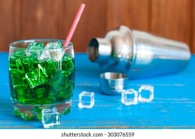 Green alcohol or alcohol-free cocktail with straw, ice cubes and shaker on a light wooden background