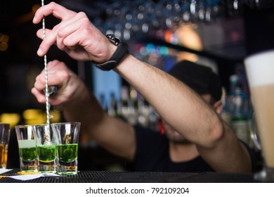 Green alcoholic cocktails is pours in restaurant