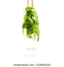Grüner Algensalat auf weißem, isoliertem Hintergrund. Hiyashi wachte. Wakamsalat mit Stäbchen für Sushi.