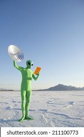 Green alien holding orange tablet with satellite dish communication system