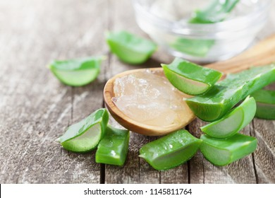 Green aloe vera leaf and fresh gel in spoon on wooden table.