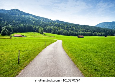 Green alpine meadow and curved asphalt road. Summer landscape