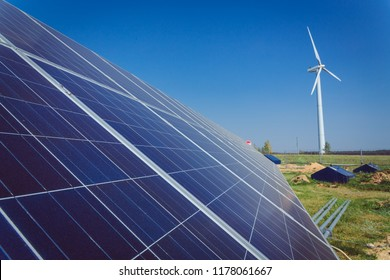 Green alternative energy and environment protection ecology concept - solar battery panels and wind generator turbines against blue sky
