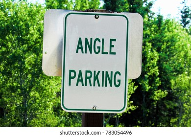 A green angle parking sign with trees in the background.