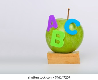 Green apple and A,B,C letters on a small book. Closeup