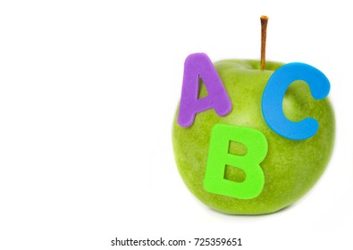 Green apple and A,B,C letters from PVC attached to it. Isolated over white. Closeup