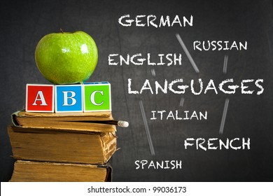 Green apple and ABC on old books against blackboard with with the drawn scheme of studying of languages. School concept