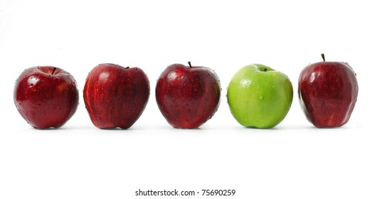 A green apple being stood out among red apples isolated on white background.