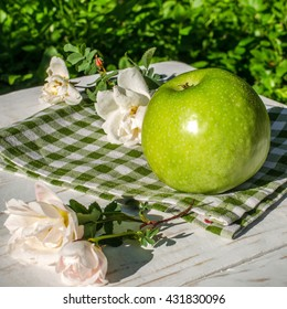 Green Apple and bright flowers of roses on the table in the garden at sunset