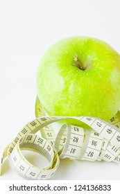green apple and centimetre on a white background