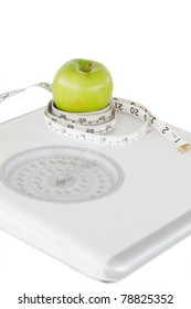 Green apple circled with a tape measure and a weigh-scale against a white background