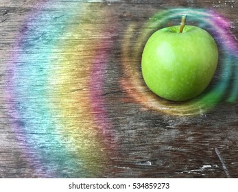 A green apple with colorful light swirls on top of grunge wooden table.