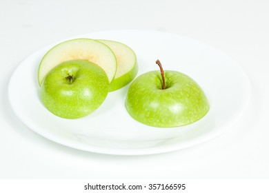 Green Apple cut in pieces in white plate.