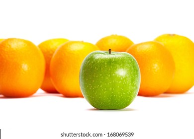 Green Apple In Front Of Oranges Conceptual Idea of Individuality - standing out of the crowd.