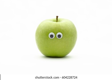 green apple with googly eyes on white background