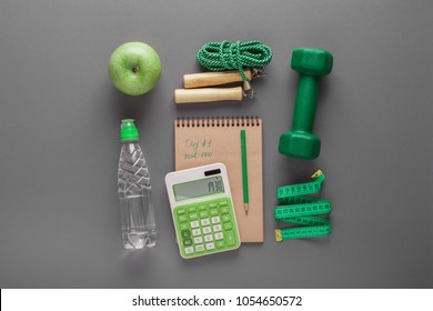 Green apple and grapefruit, green dumbbell, calculator, water bottle, tape measure, notebook, skipping rope, on a neutral background. Fitness equipment. Counting calories. Diet plan and healthy