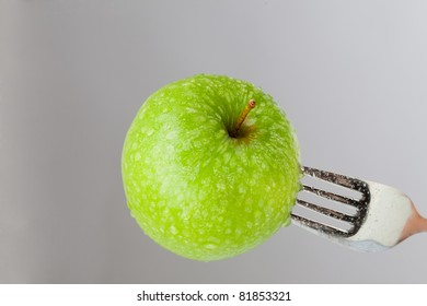 A green apple is impaled on a fork in the front of a grey Background. The green apples surface is decorated with water drops