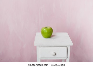 A green apple lies on a white pedestal on a pink background. A minimalistic photo.