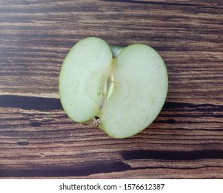 Green apple (Malus domestica) slice isolated on wallpaper background closeup. Give a sweet or sour taste Fruit is beautiful, peel, some fruit. Crispy popular eating as fresh fruit.