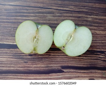 Green apple (Malus domestica) two halves slice isolated on wallpaper background closeup. Give a sweet or sour taste Fruit is beautiful, peel, some fruit. Crispy popular eating as fresh fruit.
