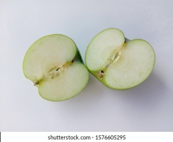 Green apple (Malus domestica) two halves slice isolated on white background closeup. Give a sweet or sour taste Fruit is beautiful, peel, some fruit. Crispy popular eating as fresh fruit.