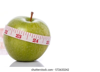 Green apple with measurement tape. Healthy concept. Studio shot isolated on white background