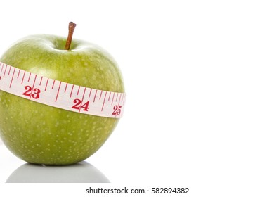 Green apple with measurement tape. Healthy concept. Studio shot isolated on white background.
