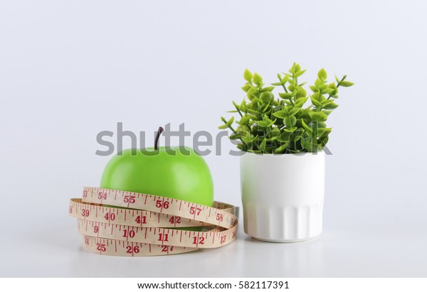 a green apple and a measurement tape on white background