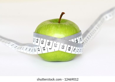 An green apple with a measuring tape around it on a white background.