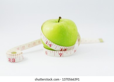 Green apple with measuring tape. Concept for diet, healthcare, nutrition or medical insurance an isolated on white background