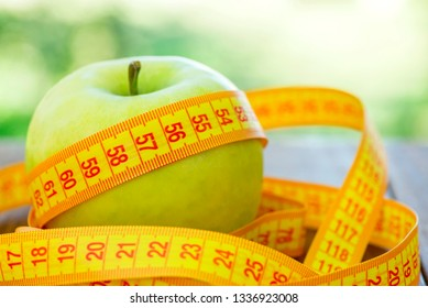 Green apple with measuring tape on wooden background. Apples and sewing tape measure on a wooden table. To lose weight and eat a low calorie apple to lose weight