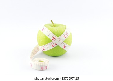 Green apple with measuring tape on over white background