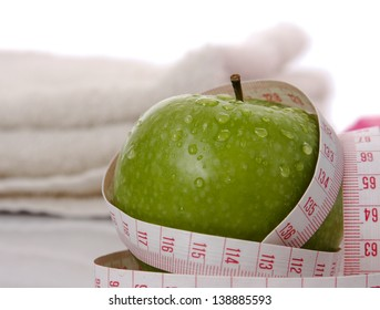A green apple and a measuring tape on a towel