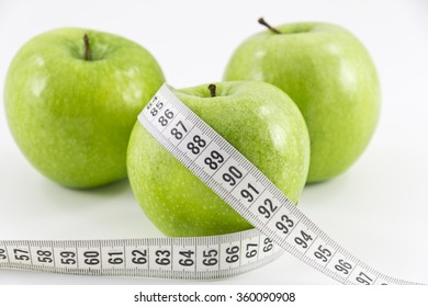 Green apple with measuring tape on white background. Green apple with measurement isolated on white. Measuring tape wrapped around a green apple as a symbol of diet. Healthy food concept.