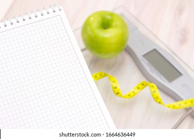 green apple, a measuring tape, scale and a notebook for writing on a light wooden background. preparation for the summer season and the beach, weight loss and sports concept