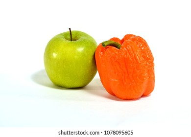 green Apple next to sluggish orange bell pepper on white background isolated.