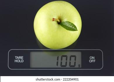 Green apple on digital scale displaying 100 gram.