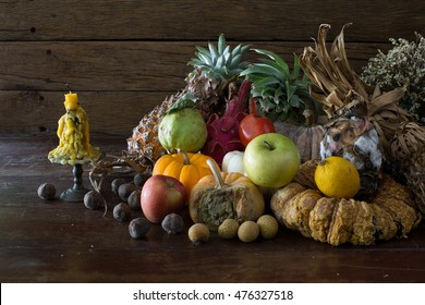 Green apple on pile rot and withered fruits in dim light on old wooden plate / Still life style