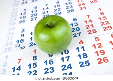 green apple on sheets of wall calendar closeup