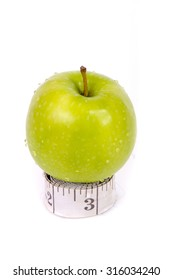 Green apple on top of measuring tape over white background. Healthy and diet concept