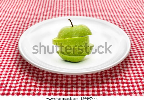 Green apple on white plate. Sliced green smith apple on a white ceramic plate on red and white checkered tale cloth.