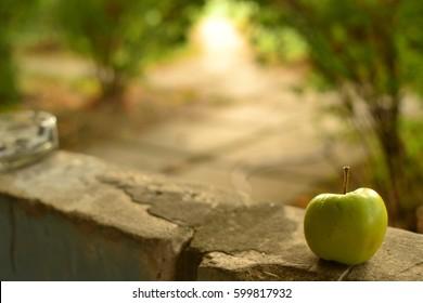 Green apple on the window sill.