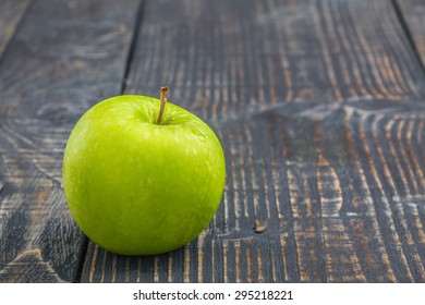 Green apple on wood background