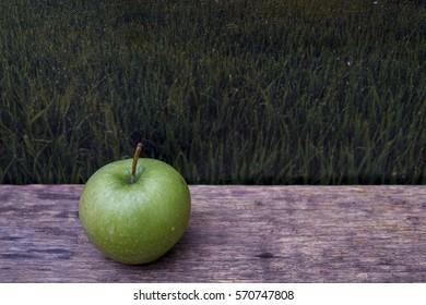 Green apple on wooden table over morning sunrise.