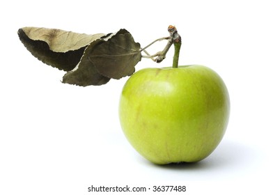 Green apple with one dry leaf isolated over white background
