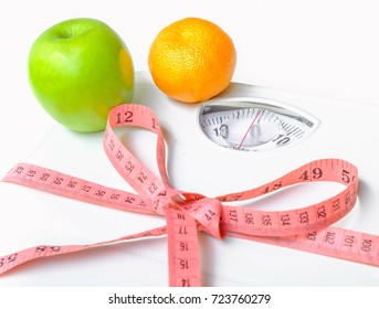 Green apple and orange Put on Weight scales tied pink measuring tape.  Selective  focus,Conception about health care