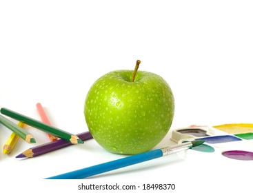 Green apple, pencils and paints  isolated on white background