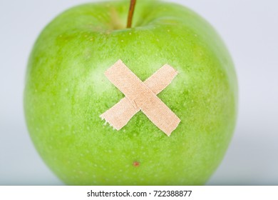 Green apple with a plaster on it. Closeup
