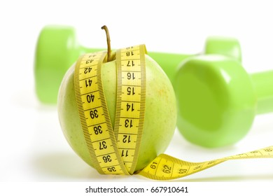 Green apple and sewing centimeter with lightweight dumbbells behind on white background representing concept of sports, diet and vegetarian nutrition